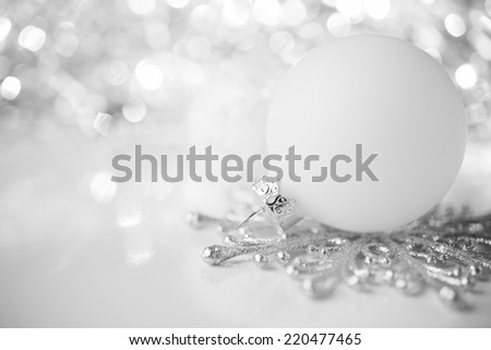 White and silver xmas ornaments on bright holiday background - stock photo