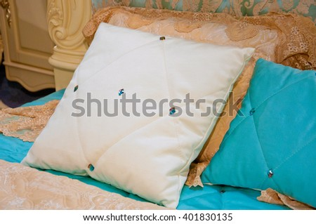 White and turquoise pillow in diamond on the bed