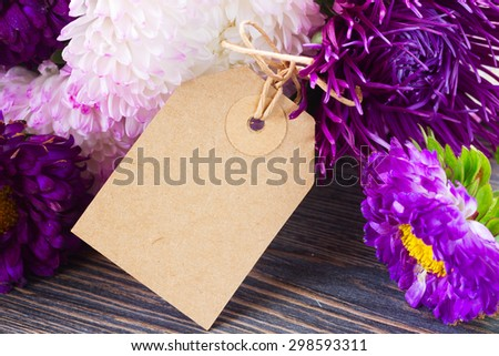 white and violet aster flowers on table with empty paper note - stock photo