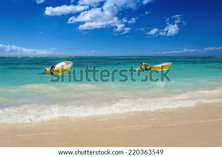 White and yellow boats on azure water of Caribbean Sea  - stock photo