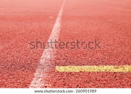 White and yellow lines and arrow. Textured red rubber of running racetracks in outdoor stadium - stock photo