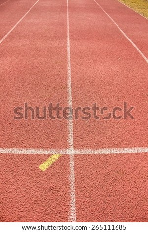 White and yellow lines and texture of running racetrack, red rubber racetracks in outdoor stadium - stock photo