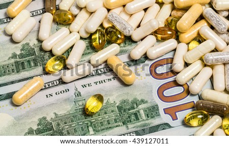 White and yellow macro drug pills and fish oil capsules on one hundred dollars banknotes as a background. Money and medicine still life concept. - stock photo