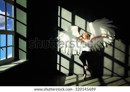 White Angel and Day Light on Black Background - stock photo