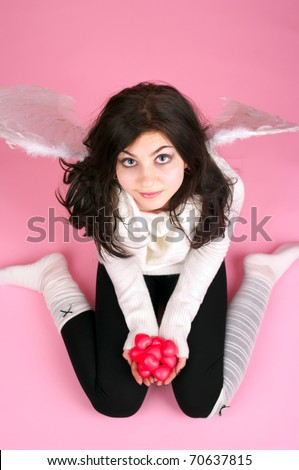 White angel girl with small red hearts in the hand - stock photo