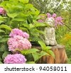 White Angel Statue on Tree Stump in the Garden with Pink Hydrangea Flowers - stock photo