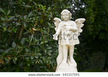 White angel statue tosses flower petals in the garden of the Catholic San Fernando Mission in Los Angeles, California - stock photo