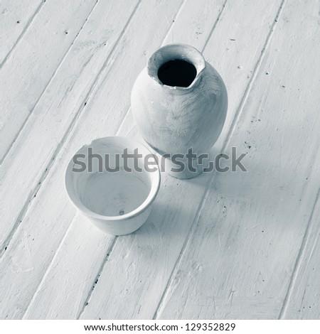 White antique jugs on the white floor. - stock photo
