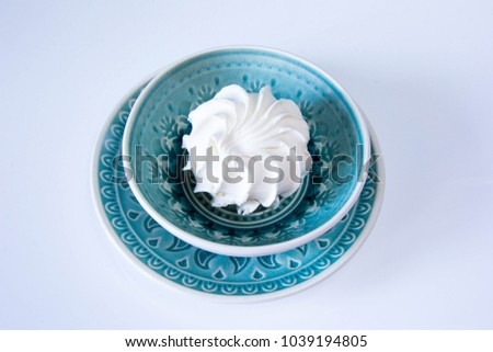 White apple zephyr at ethnic blue plate at white background