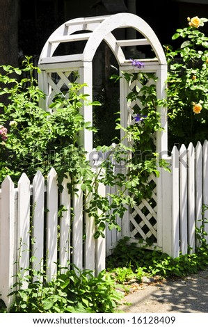 White arbor with blooming roses in a garden - stock photo
