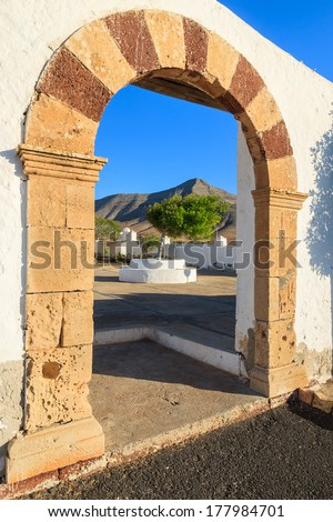 White arch gate with mountain framed, entrance to small church in Tefia village, Fuerteventura, Canary Islands, Spain - stock photo