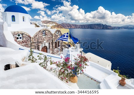 White architecture on Santorini island, Greece. Beautiful landscape with sea view, blue dome church and Greece flag. - stock photo