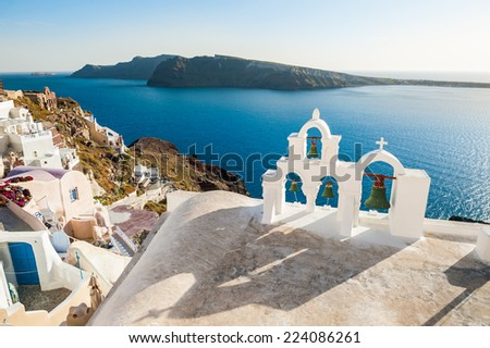 White architecture on Santorini island, Greece. Bell tower in Oia town. Beautiful view on the sea