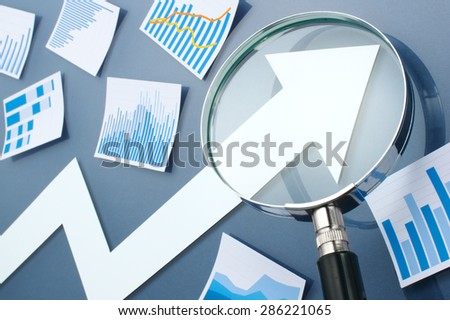 White arrow and magnifying glass. Many blue graphs and charts. Looking growth arrow with magnifying glass. Concept image of growth strategy.  - stock photo