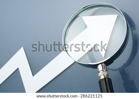 White arrow and magnifying glass on dark blue background. Looking upside growth arrow with magnifying glass. Concept image of growth potential.  - stock photo