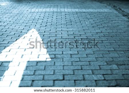 White arrow straight forward on block street vintage retro tone in blue tone  - stock photo