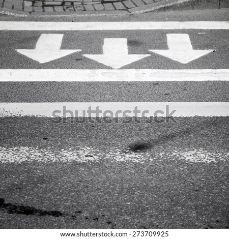 White arrows and lines on dark gray asphalt road, pedestrian crossing road marking - stock photo