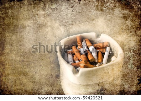 White ashtray full of cigarette with a grunge texture of scratches added for effect - stock photo
