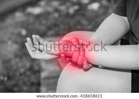 white asian fitness fat woman holds her wrist, wrist pain,wrist injury. - stock photo