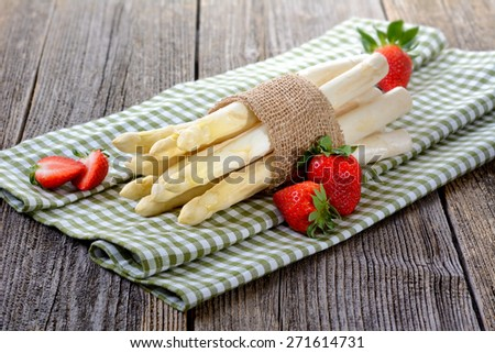 White asparagus of Germany with strawberries on a wooden table - stock photo