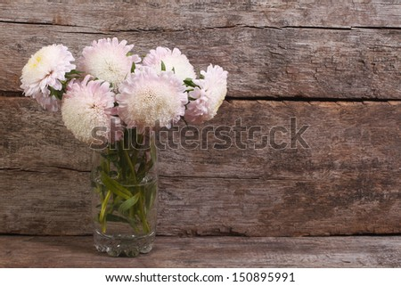 white asters in a glass on a background of the old wooden planks