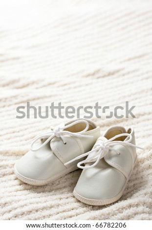 White baby shoes sitting on blanket. - stock photo