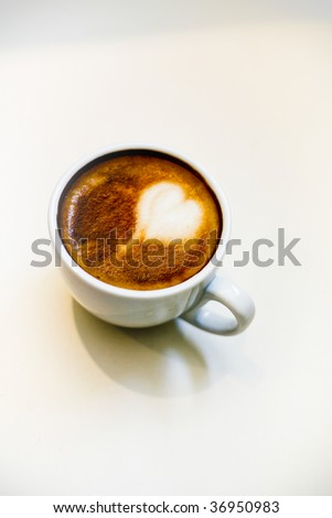 white background and fresh cappuccino with a heart shaped in the top of the frothy steamed milk - stock photo