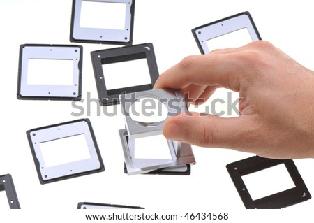 White background studio image of a photographer reviewing empty slides on lightbox. - stock photo