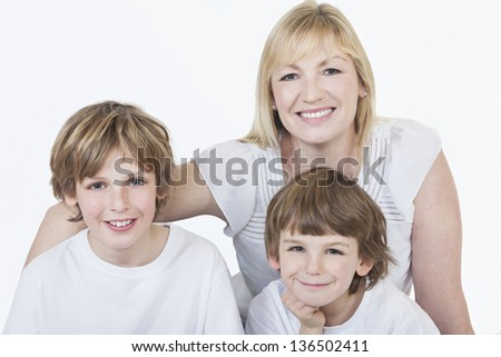 White background studio photograph of young happy family mother and two boy sons smiling