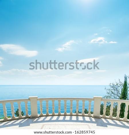 white balcony near sea and light clouds on sky - stock photo