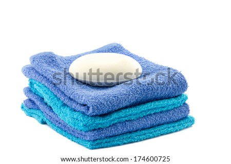 white bar of soap on top of piled towels - stock photo