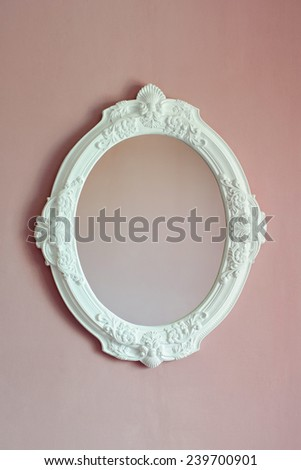 white baroque oval frame are on the pink wall - stock photo