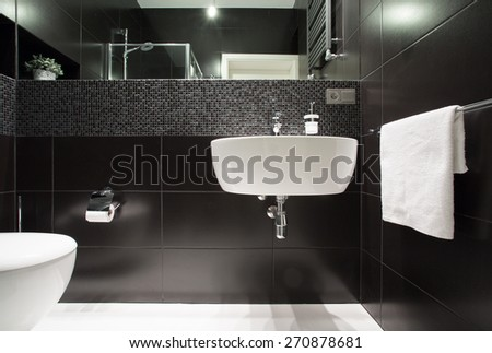 White basin on black wall in modern bathroom - stock photo