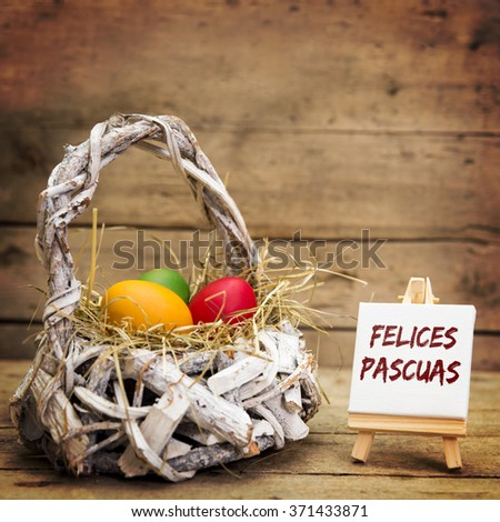 white basket with easter eggs, canvas with spanish text felices pascuas, which means happy easter, wooden background - stock photo
