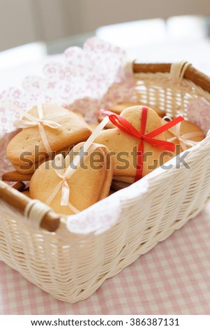 White basket with homemade crispy cookies decorated with thin ribbons. Cookies on the table. Preparations for holiday season. Baking at home. - stock photo