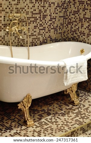 White bath beautiful form with gilt legs and mixer for making of water procedures - Interior of a bathroom in retro style. - stock photo