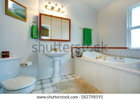 White bathroom with white bath tub, toilet and washstand. Decorated with green towels - stock photo