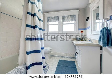 White bathroom with white washbasin cabinet, blue rug and striped curtains. - stock photo