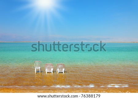 White beach armchairs and a chair in the warm clear water beach. Beach at the Dead Sea,  sunny day in May - stock photo