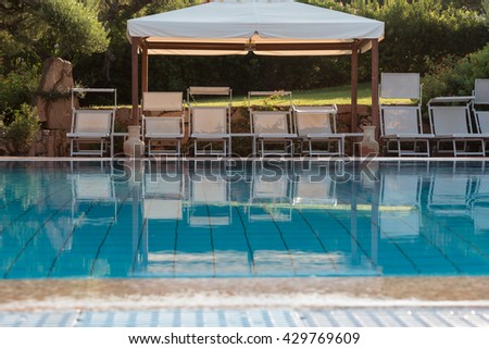 White Beach Loungers in Line under Big Awning near Swimming Pool, Beach Chairs - stock photo