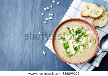 White beans chicken soup on a dark wood background. toning. selective focus - stock photo