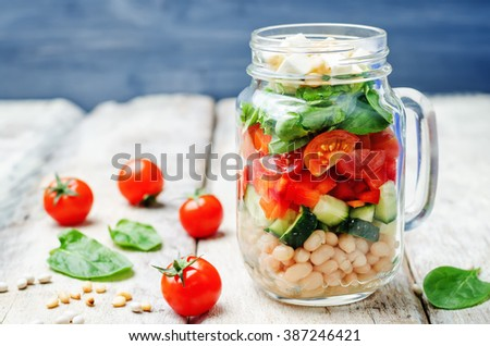 White beans cucumber tomato red pepper feta spinach salad in a jar. toning. selective focus - stock photo