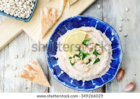 white beans hummus with lemon on white wood background. toning. selective Focus - stock photo