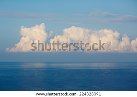 White beautiful clouds drifting across the blue sky reflected in the calm sea  on a sunny summer day - stock photo