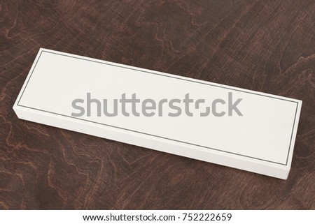 White beautiful paper box, mock-up, blank on a wooden background, with reflection