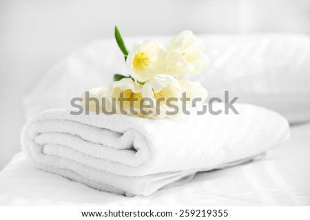 White beautiful tulips on fresh towels in hotel, close up - stock photo