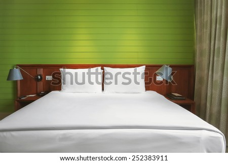 white bed in green room - stock photo