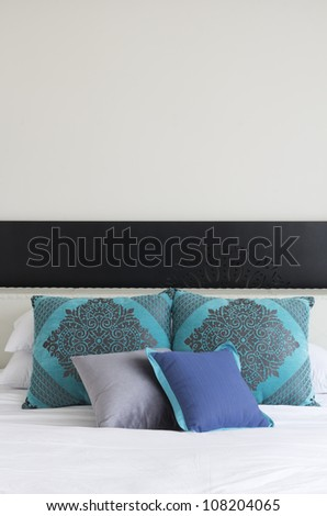 White Bed with White and Blue decorated Pillows - stock photo