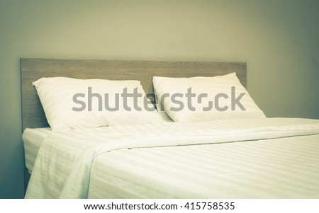 white bedding and pillow in hotel room , vintage tone