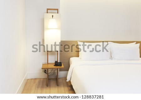 white bedroom with wood floor and furnitures. - stock photo